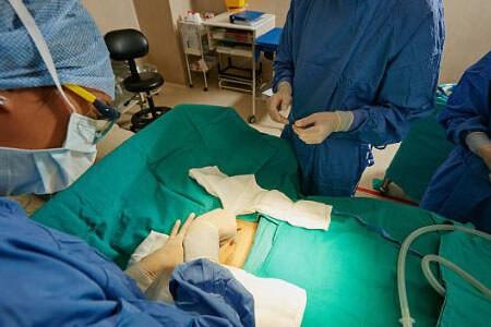 Хирург делает разрез живота