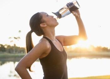 Девушка пьет во время бега