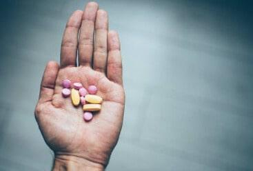 Рука с таблетками на ладони