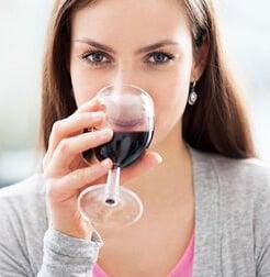 Девушка пробует крепкое вино
